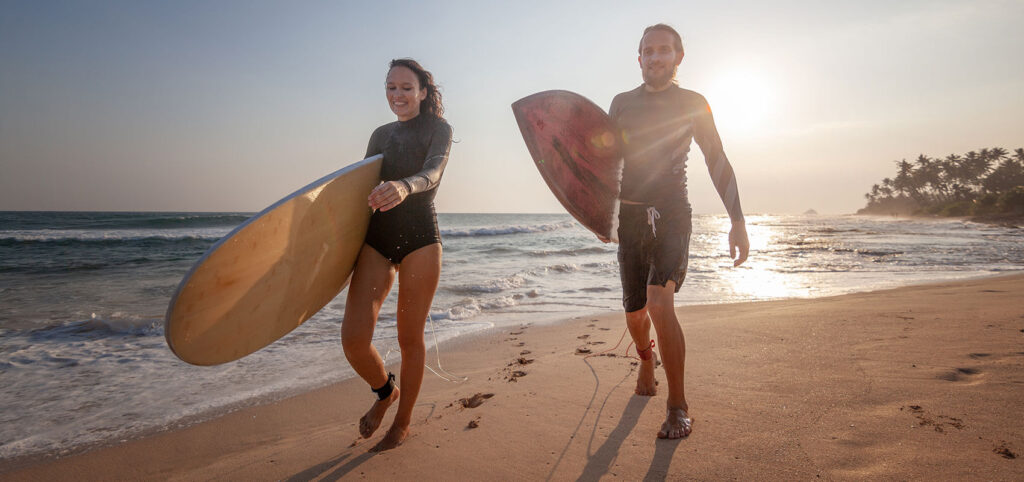 White couple on beach carrying surf boards