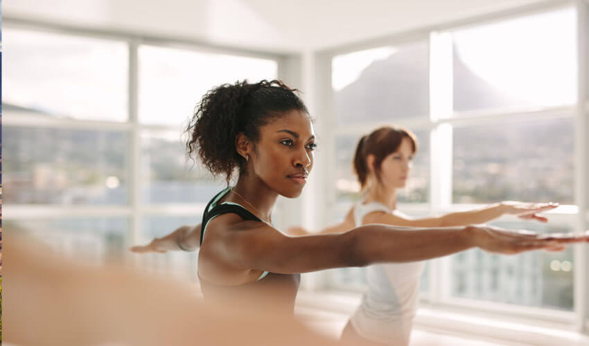 Black woman in foreground, white woman in background doing yoga in studio